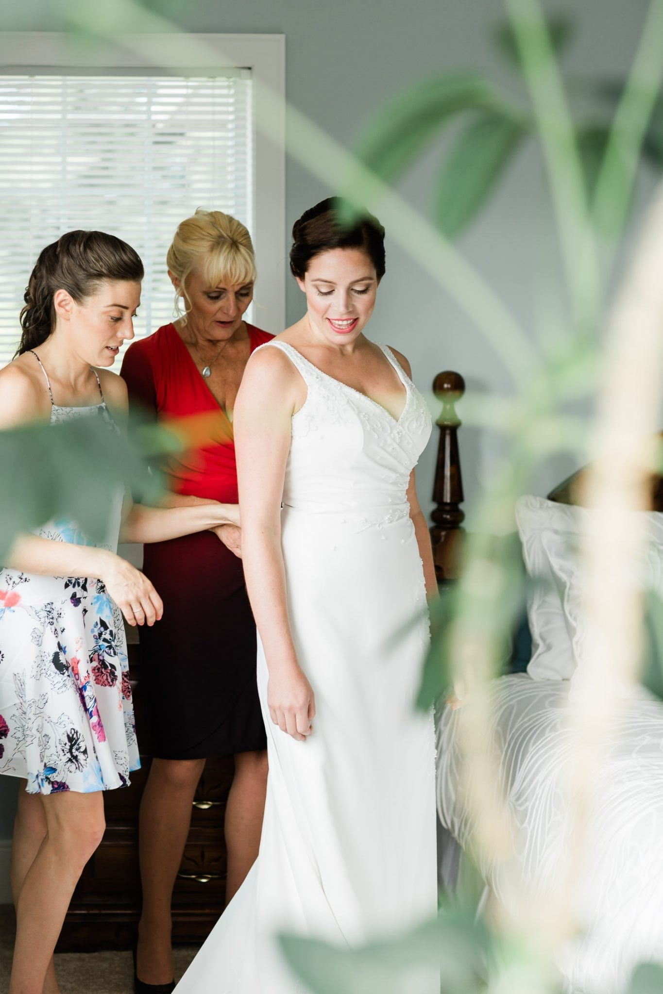 Brides mate helping with a dress | Vancouver wedding photographer