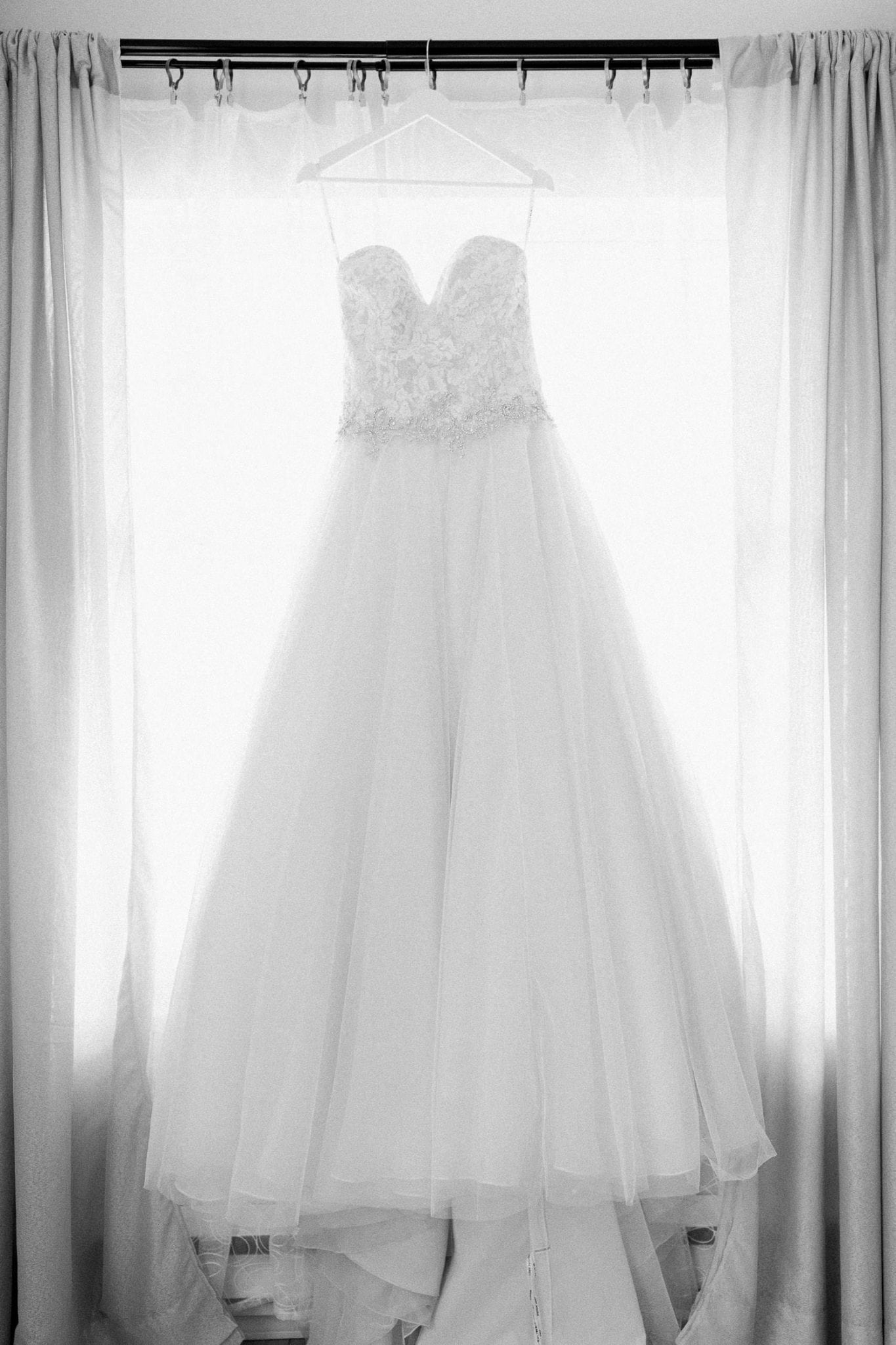 Picture of the wedding dress hanging in front of the window in b/w | Vancouver wedding photographer | Westwood Plateau Golf Club Wedding