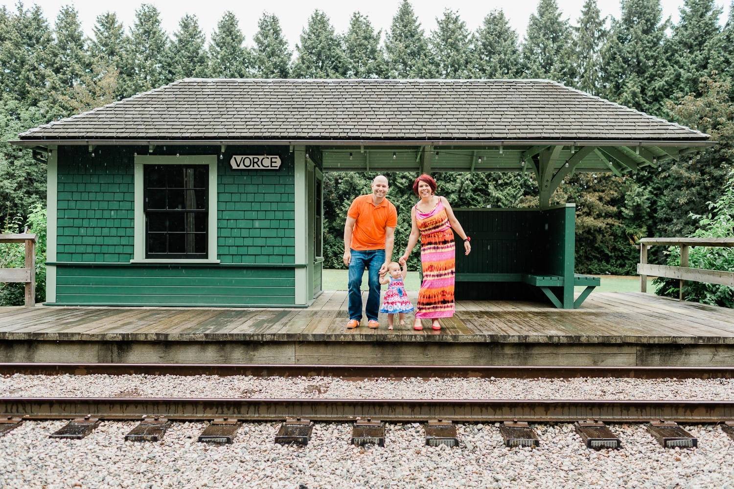 Couple standing on the old railway station holding a baby. Family Photo in Burnaby Village Museum