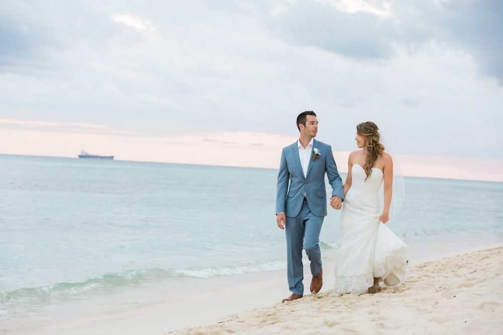 Bride and groom walking on the beach photo in Mexico | Vancouver wedding photographer