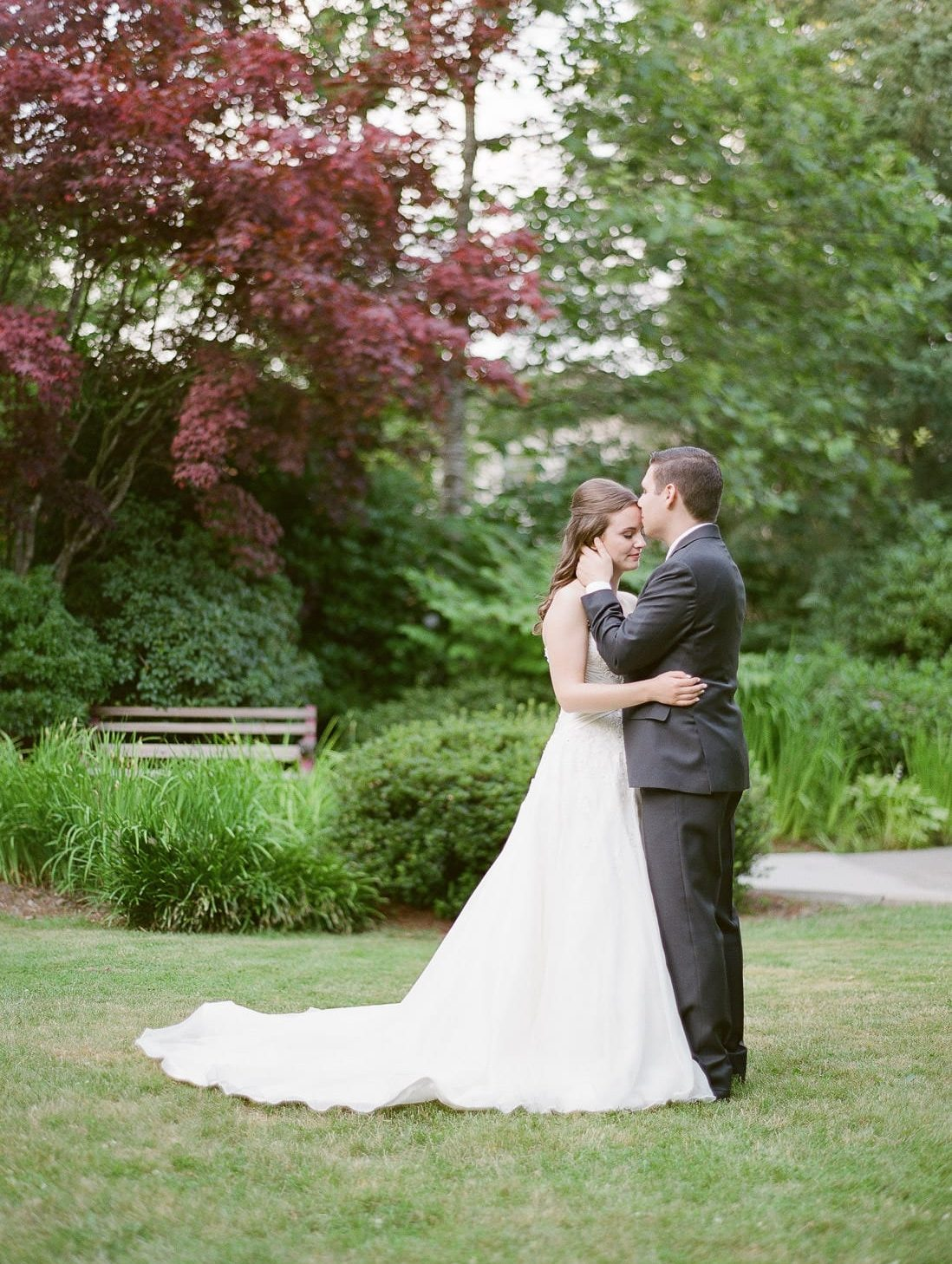 a couple posing in the park with gazebo in Maple Ridge, holding each other during wedding photo session