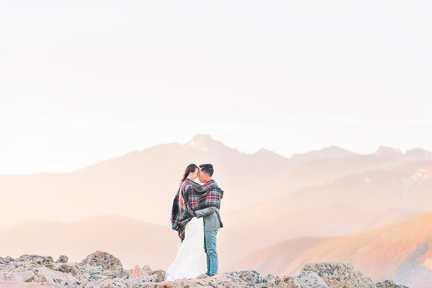 bride and groom holding each other with the blanket on the shoulders with the best photography location at the background